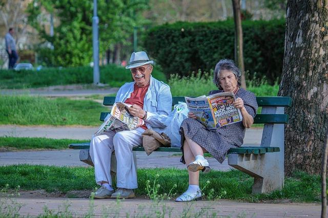 důchodci s novinami